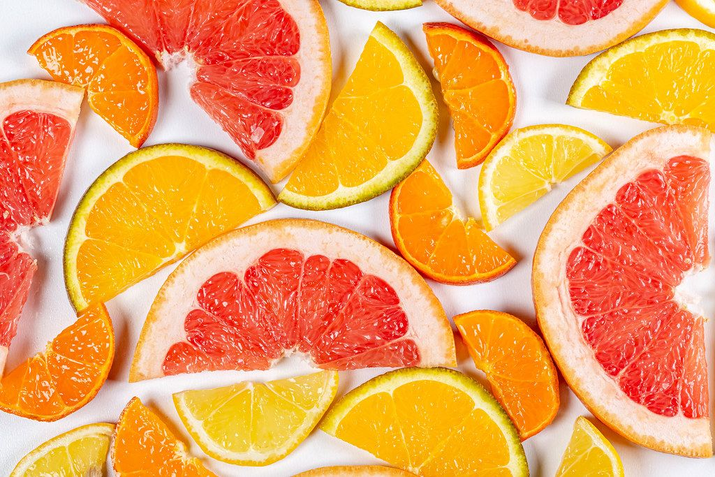 Citrus background with slices of juicy fresh fruit, top view