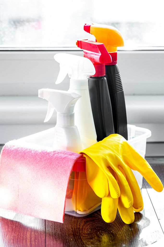 Cleaning products with rubber gloves in the kitchen by the window