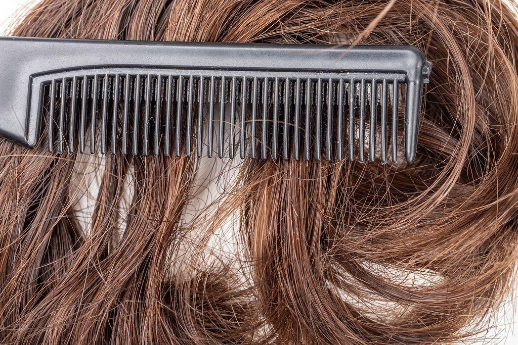Close- up, black comb on dark female hair (Flip 2020)