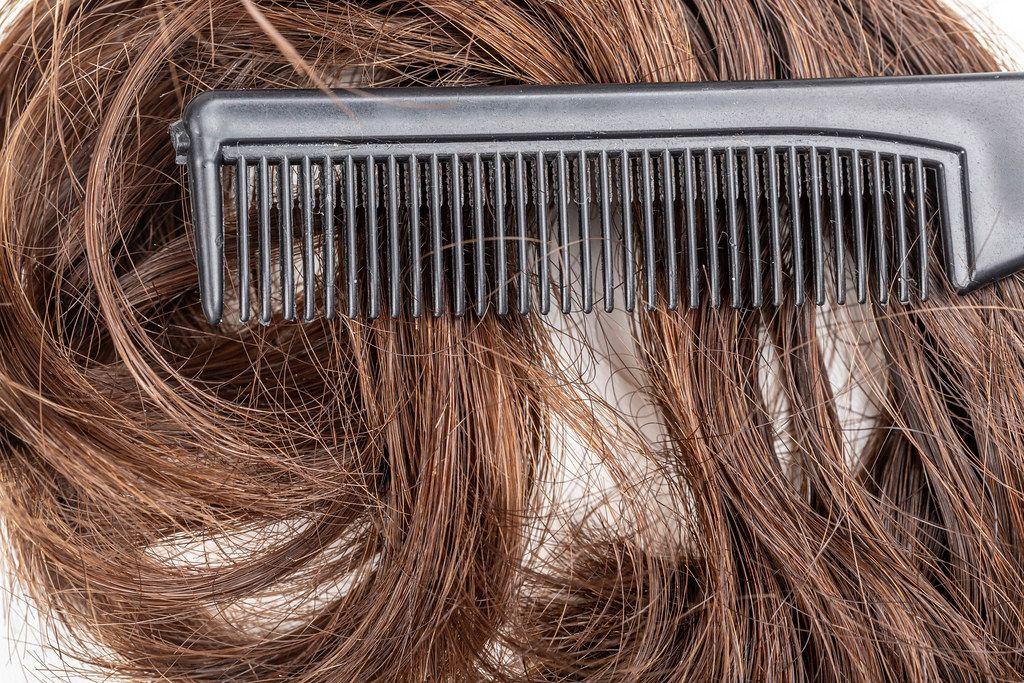 Close-up-black-comb-on-dark-female-hair.jpg