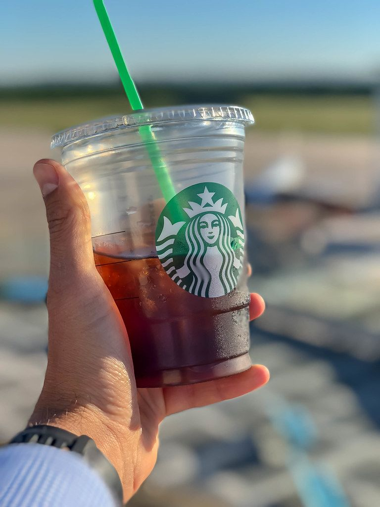 Close Up Bokeh Photo of Hand holding a Plastic Cup with Starbucks Cold Brew Coffee with Plastic Straw