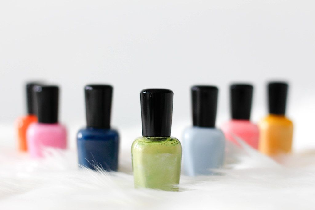 Close Up Bokeh Photo of Nail Polish in different Colors on white Fur on white Background