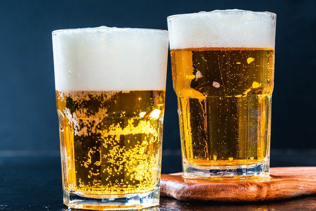 Close Up Bokeh Photo of Two Glasses of Beer with Foamy Top Layer on Dark Background