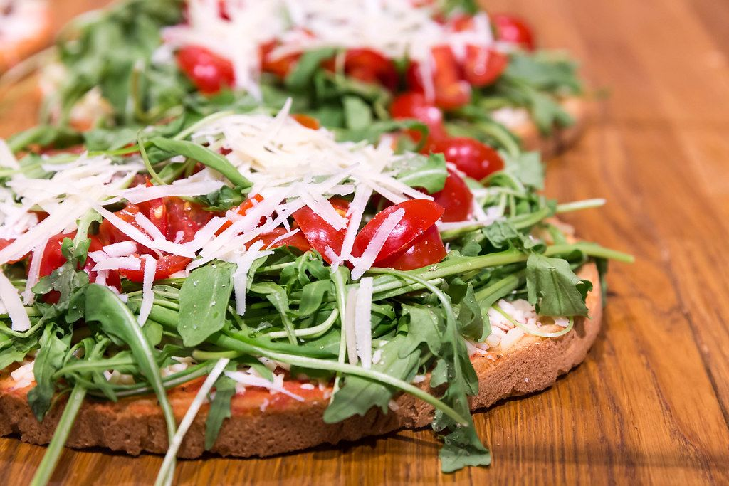 Close Up Food Photo of Bruschetta Fresca with Arugula, Cherry Tomatoes and Parmesan Cheese