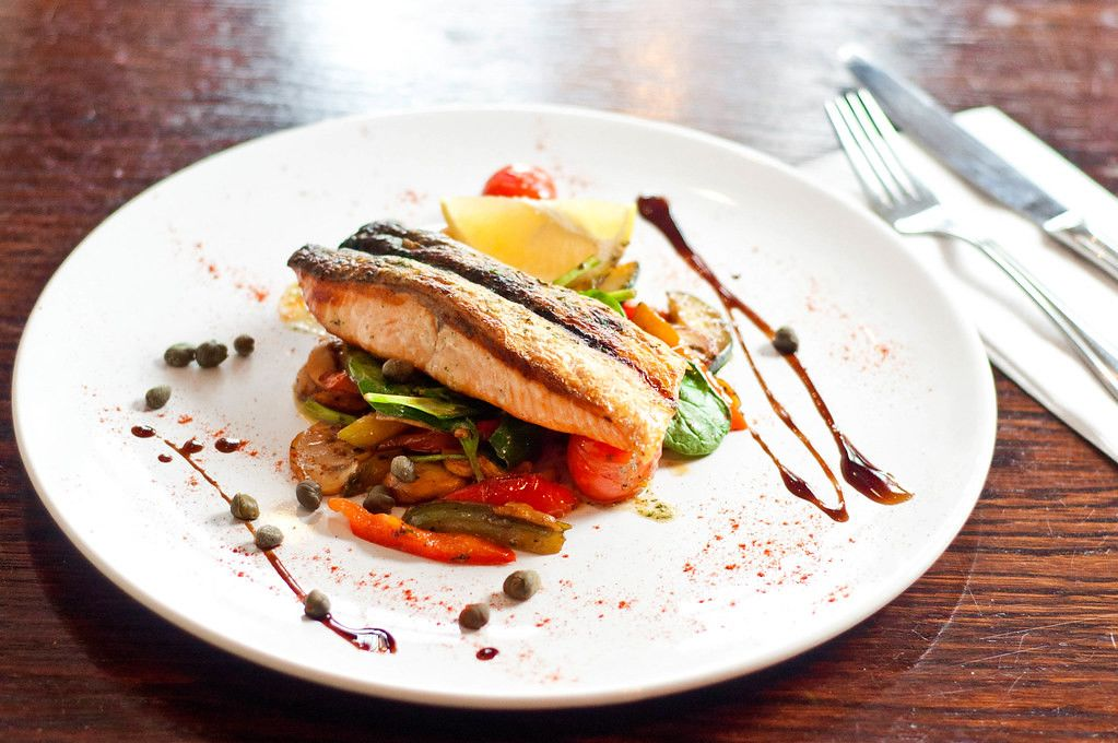 Close Up Food Photo of Fried Fish with Vegetables on beautifully decorated plate at Fancy Restaurant