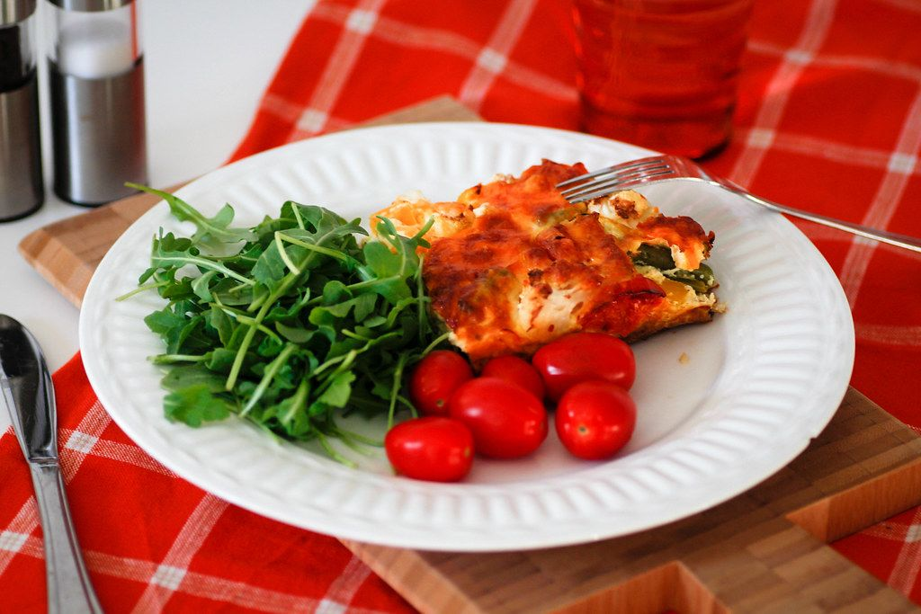 Close Up Food Photo of Quiche with Arugula Salad and Cherry Tomatoes on a White Plate with Fork and Knife
