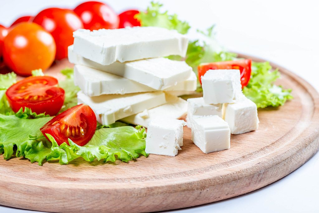 Close Up Food Photo of Stack and Cubes of Feta Cheese, Cherry Tomatoes and Lettuce on Wooden Cutting Board