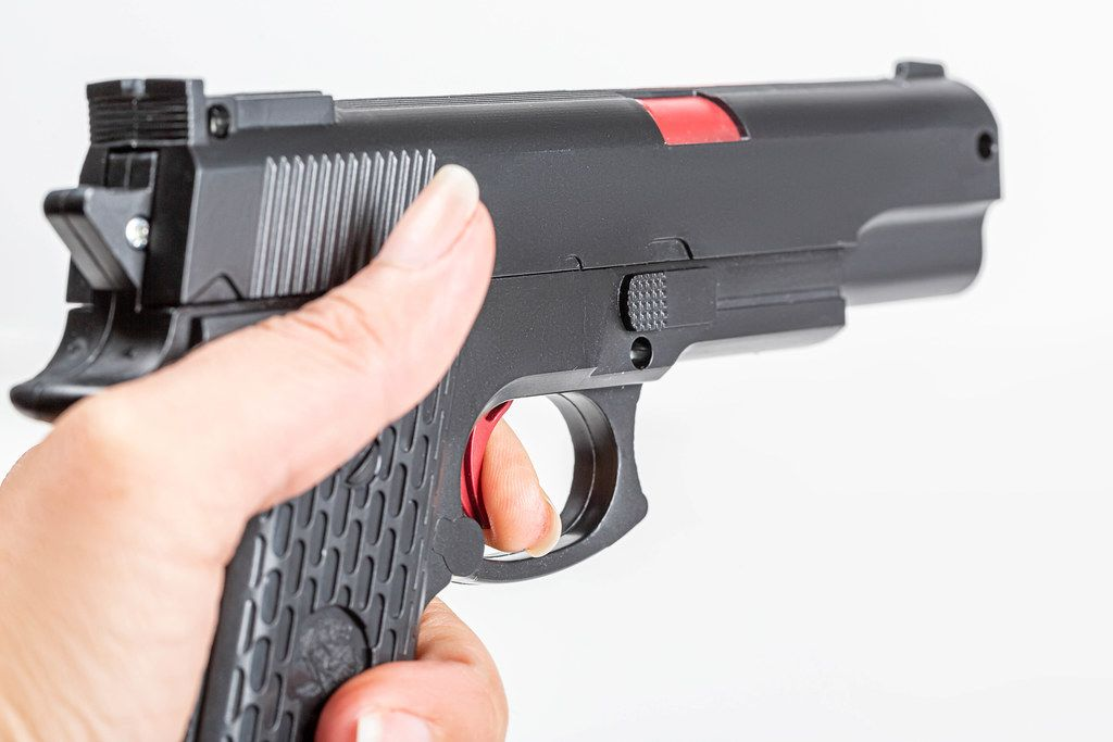 Close up, hand holding black plastic toy gun
