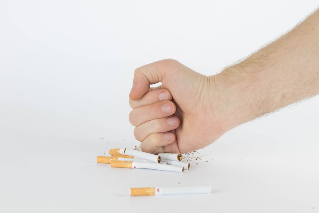 Close-up man hand crushing a pile of cigarettes