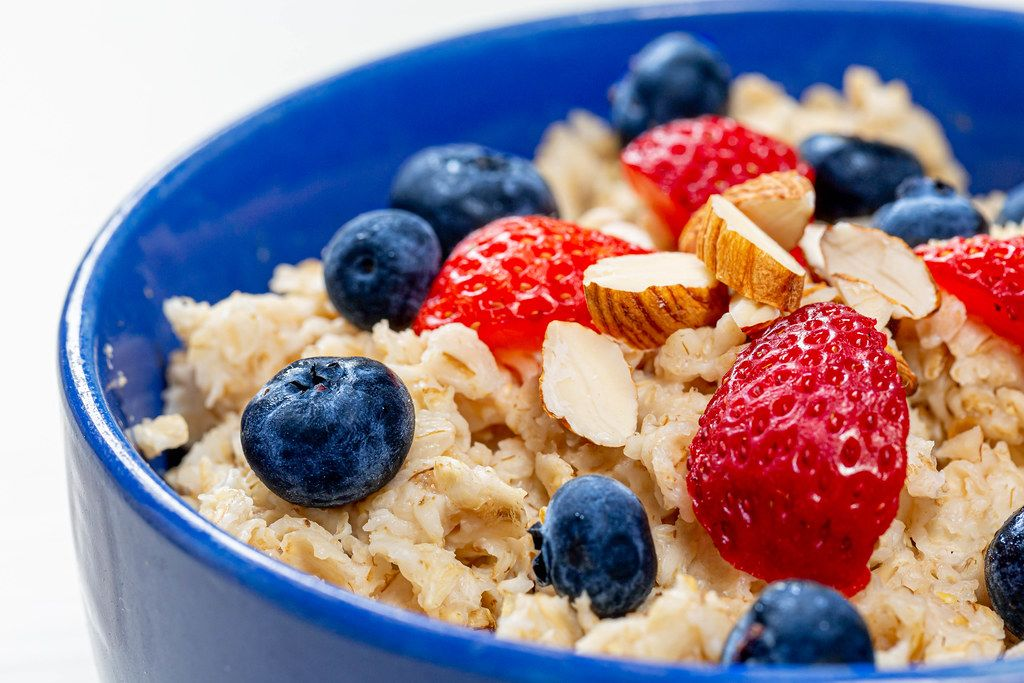 Close-up oatmeal porridge with blueberries, almonds and strawberries