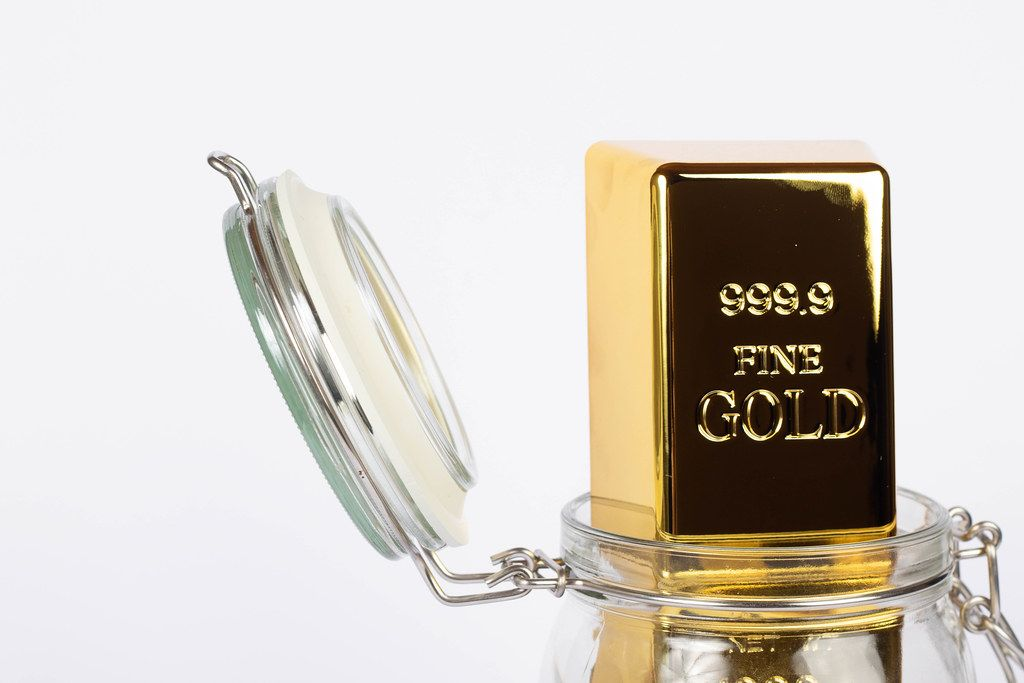 Close up of a gold bar in a glass jar on a white background