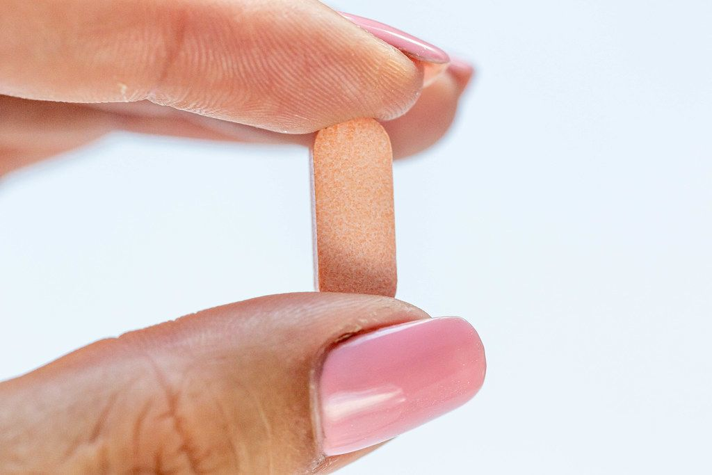 Close-up of a pink tablet in the hand of a girl with a pink manicure