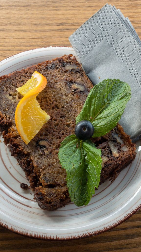 Close-up of a slice of banana bread, garnished with mint leaves and an orange slice