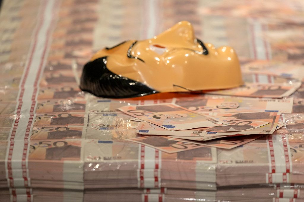 Close-up of a stack of money and a Salvador Dali mask, famous from Netflix crime show Money Heist