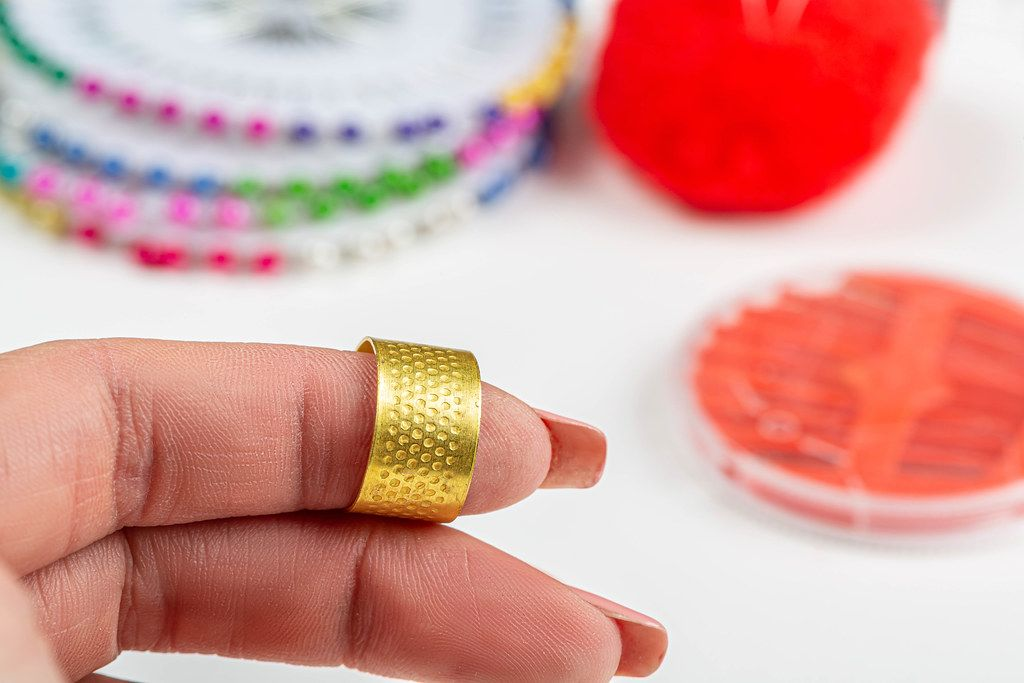 Close-up of a thimble for sewing on a woman's finger