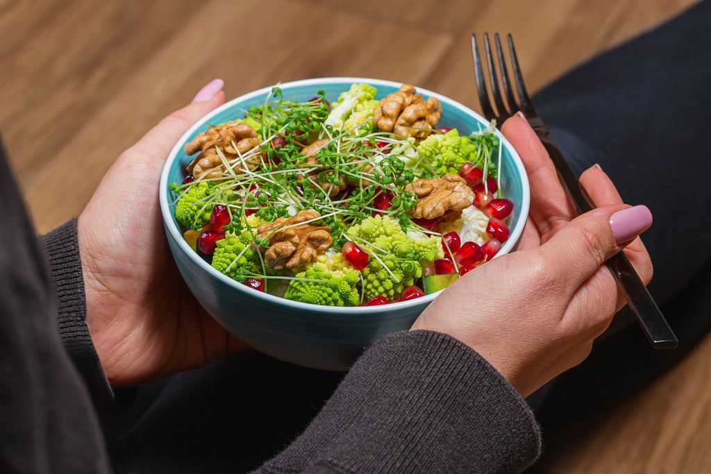 Close-up of a vegetable salad with nuts and micro greenery in a woman's hands with a black fork. Dietary food