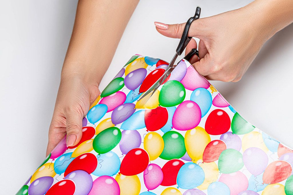 Close-up of a woman cutting gift wrapping paper with scissors (Flip 2019)