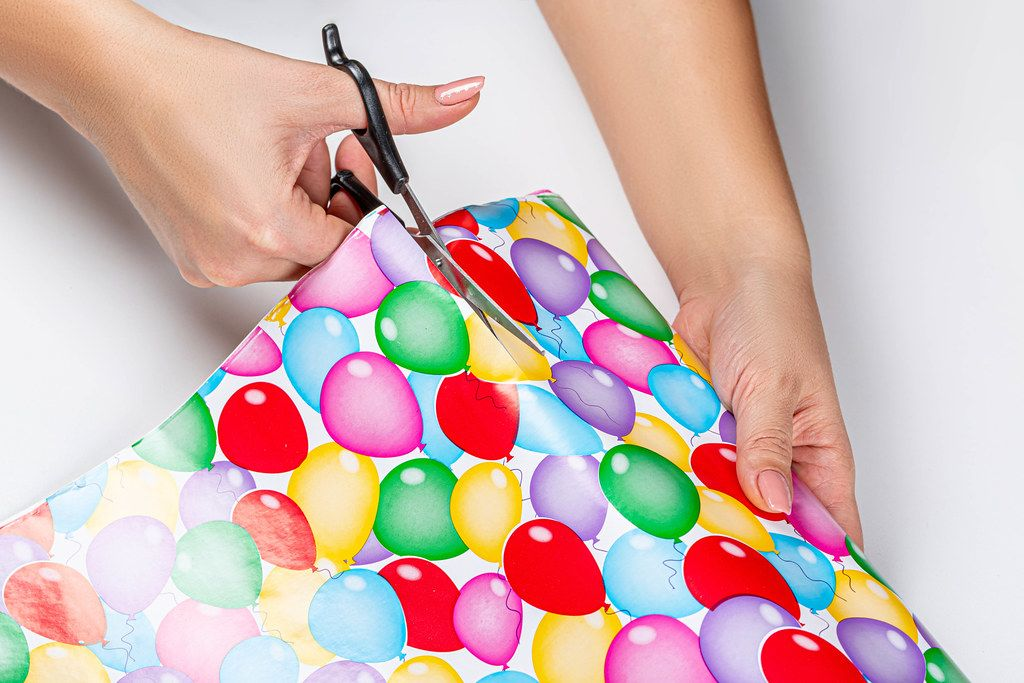 Close-up of a woman cutting gift wrapping paper with scissors