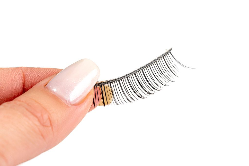 Close up of a woman's hand holding false eyelashes