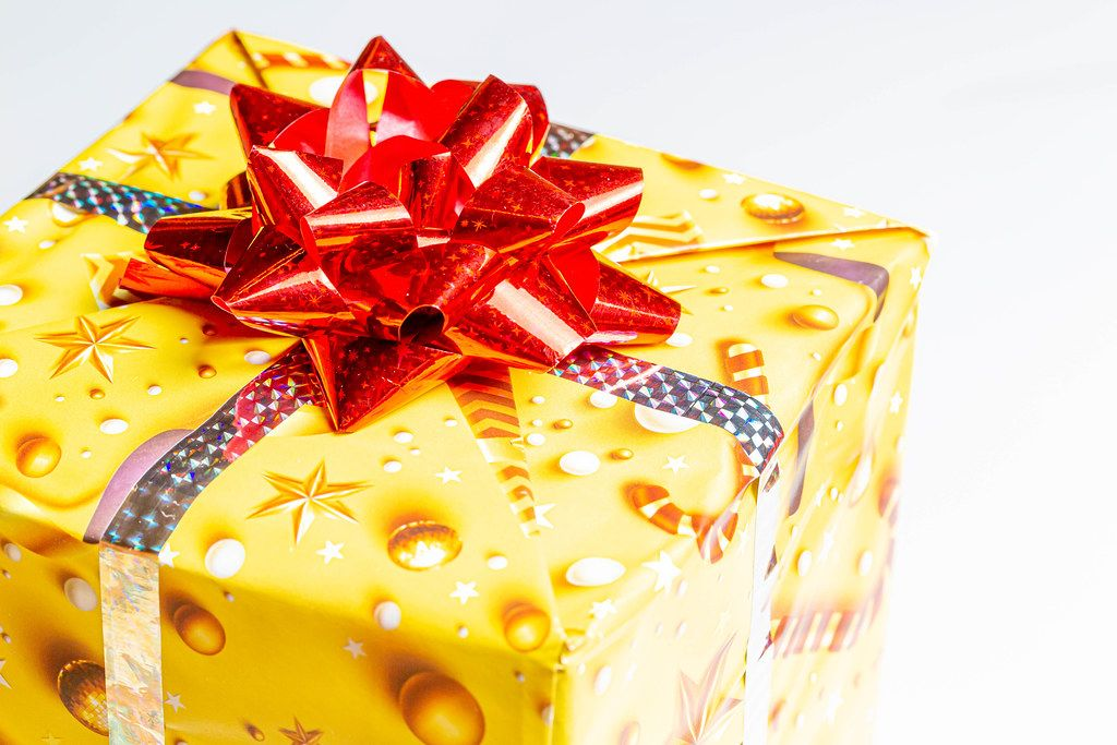Close-up of a yellow gift box with a red bow