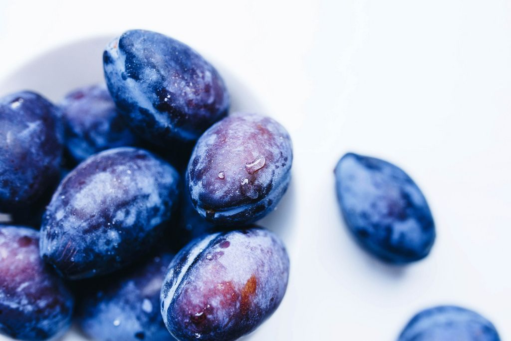 Close up of blue plums and water drops on them