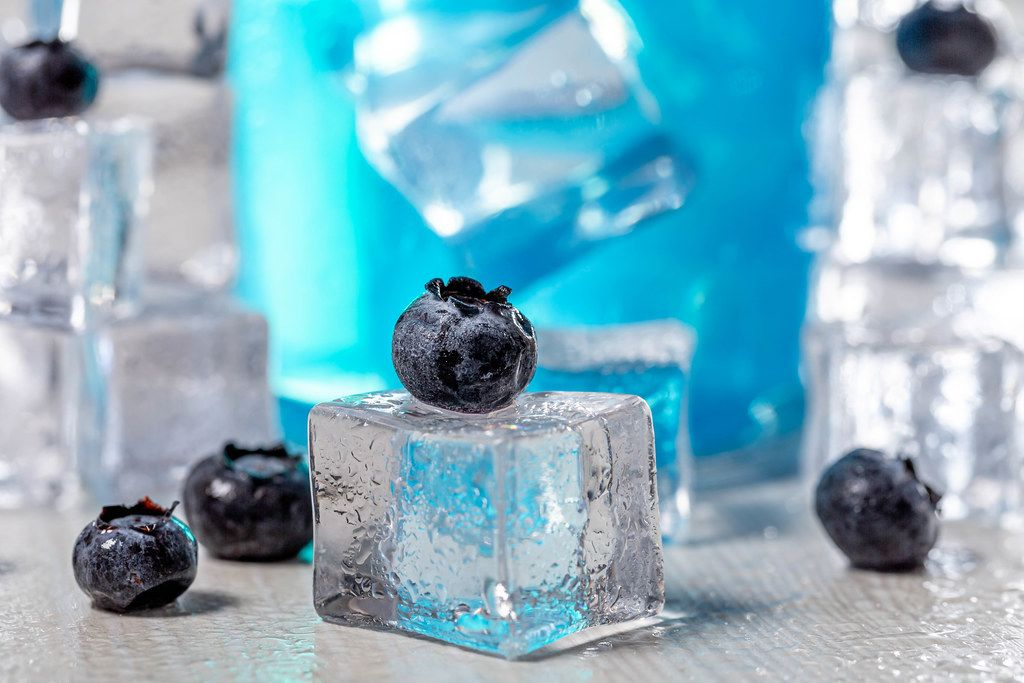 Close-up of blueberries on ice cube with blue cocktail behind (Flip 2019)