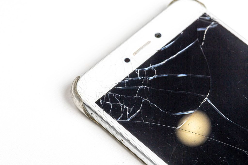 Close up of broken mobile phone screen on white background