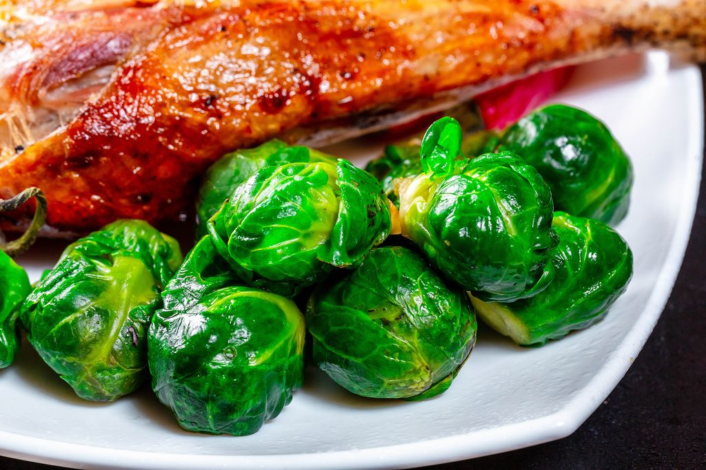 Close-up of Brussels sprouts with baked chicken leg
