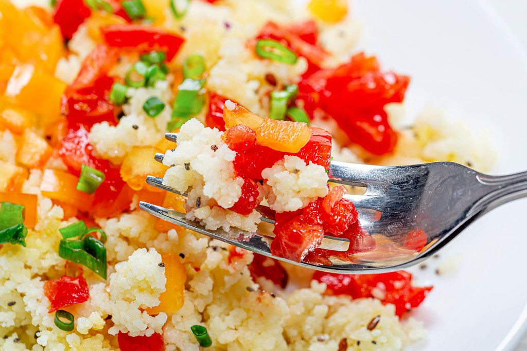 Close up of cooked porridge couscous with vegetables on a fork