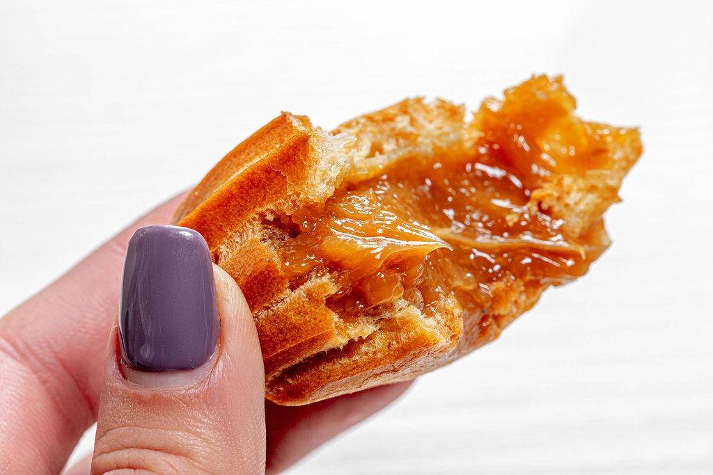 Close up of eclair with condensed milk in a woman's hand