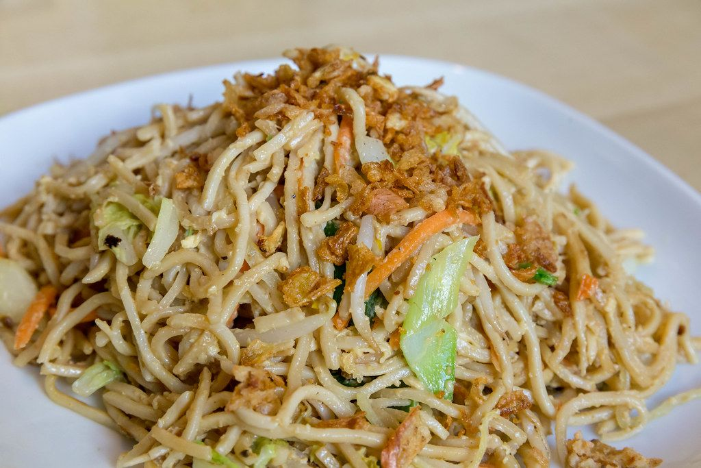 Close-up of fried Asian noodles with fried egg and lots of vegetables, as vegetarian lunch