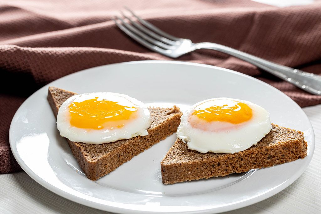 Close-up of fried eggs on pieces of black bread