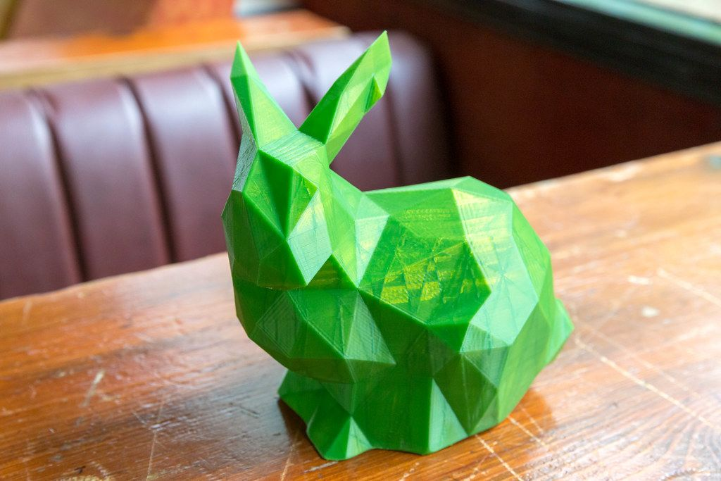 Close-up of green rabbit printed by a 3D printer on a wooden table