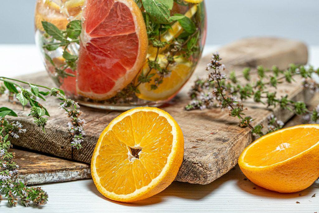 Close-up of half oranges, fresh mint and a jug of lemonade