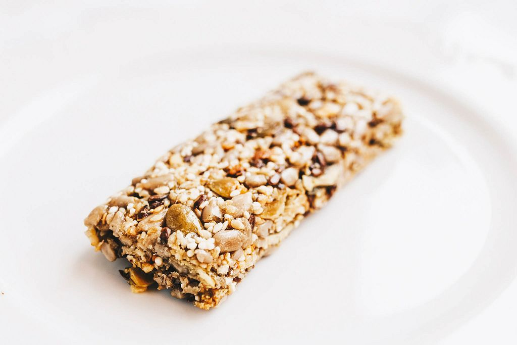 Close up of healthy muesli bar with nuts on white background