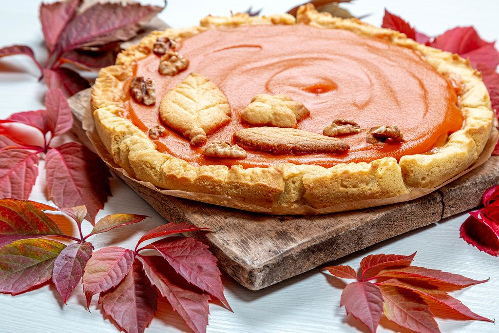 Close - up of homemade pumpkin pie on an old kitchen Board with colorful autumn leaves. The concept of the autumn holidays