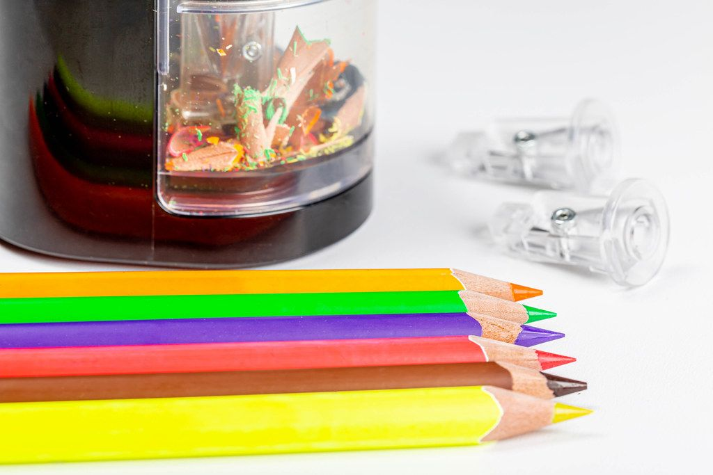 Close-up of multi-colored pencils with an electronic sharpener