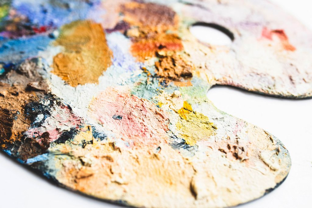 Close up of oil paint on painter's palette on white background