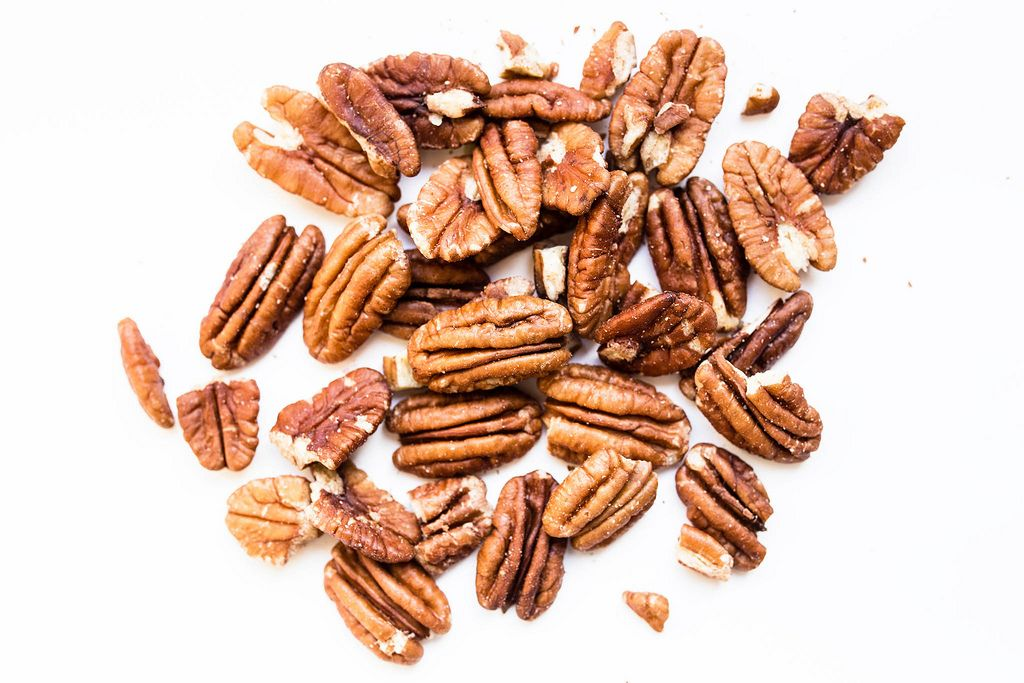 Close up of raw pecan nuts on white background