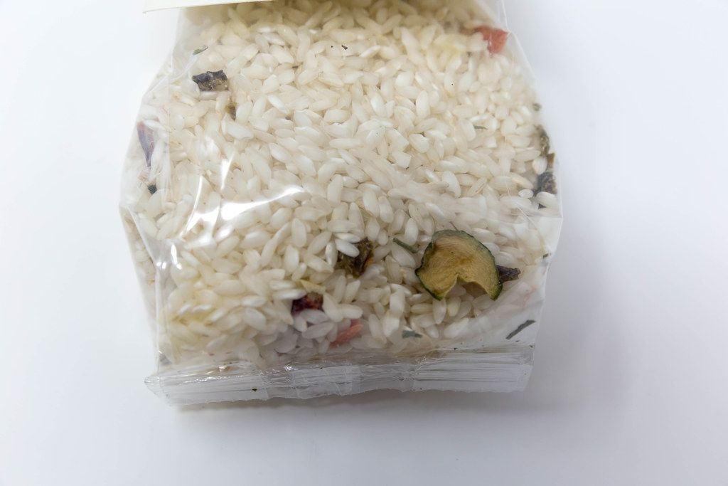 Close up of raw Risotto Mediterraneo mix with vegetables by Casale Paradiso, in plastic packaging, with white background
