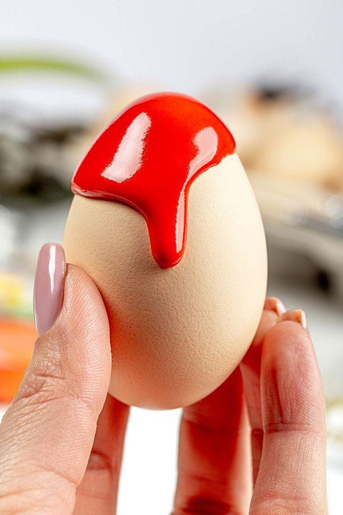 Close-up of red paint flowing down a chicken egg in a female hand