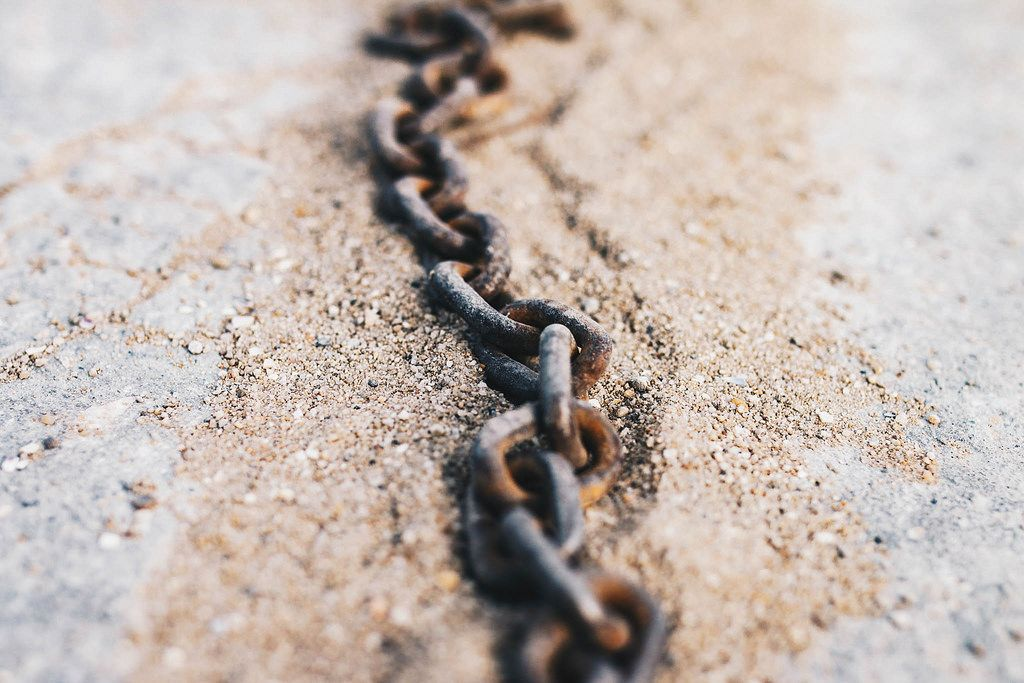 Close up of rustic chain in the sand