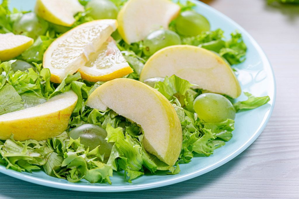 Close-up of salad with apples, grapes and lettuce in a blue plate