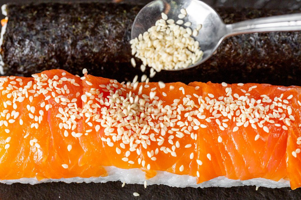 Close-up of sesame pours on sushi roll with salmon (Flip 2019)