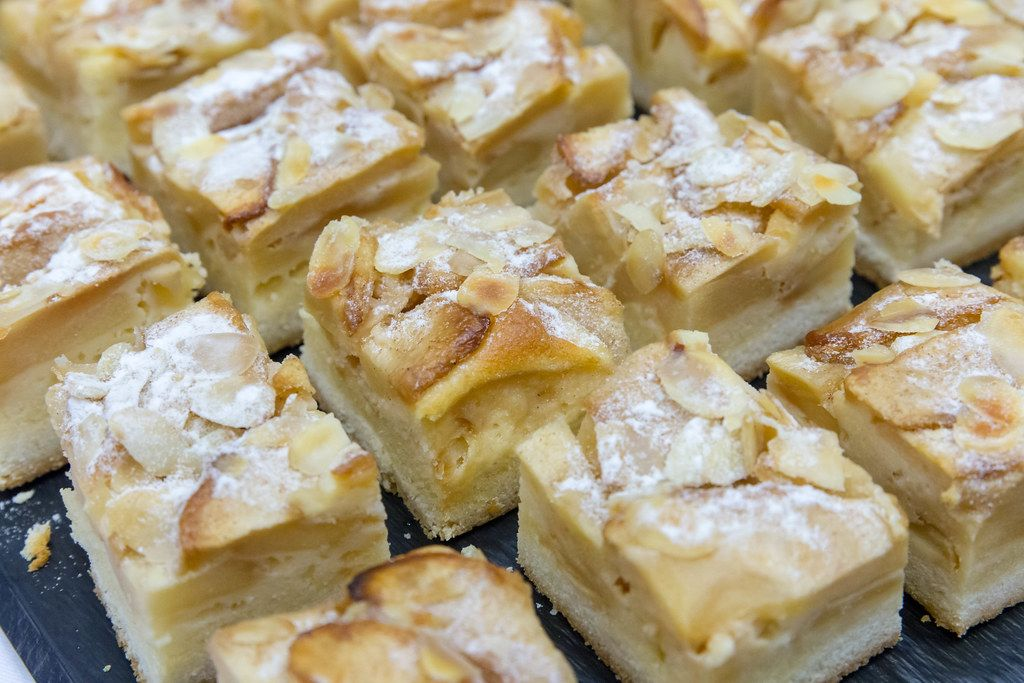Close-up of several pieces of almond-apple cake with icing sugar
