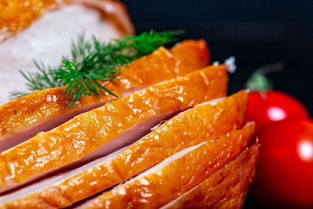 Close-up of sliced smoked chicken on dark background