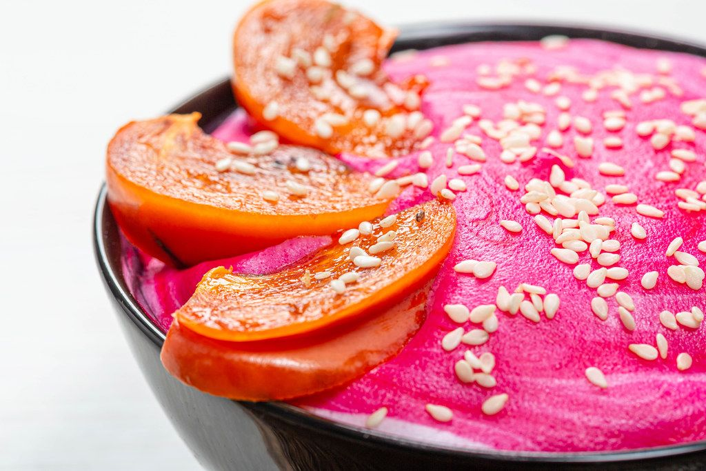 Close-up of slices of persimmon and sesame seeds on pink yogurt. Beautiful oatmeal for Breakfast