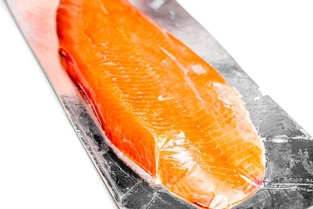 Close-up of smoked red fish fillet on white background