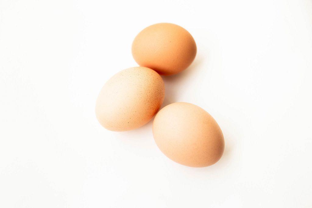 Close up of three eggs isolated on white background (Flip 2019) (Flip 2019) Flip 2019