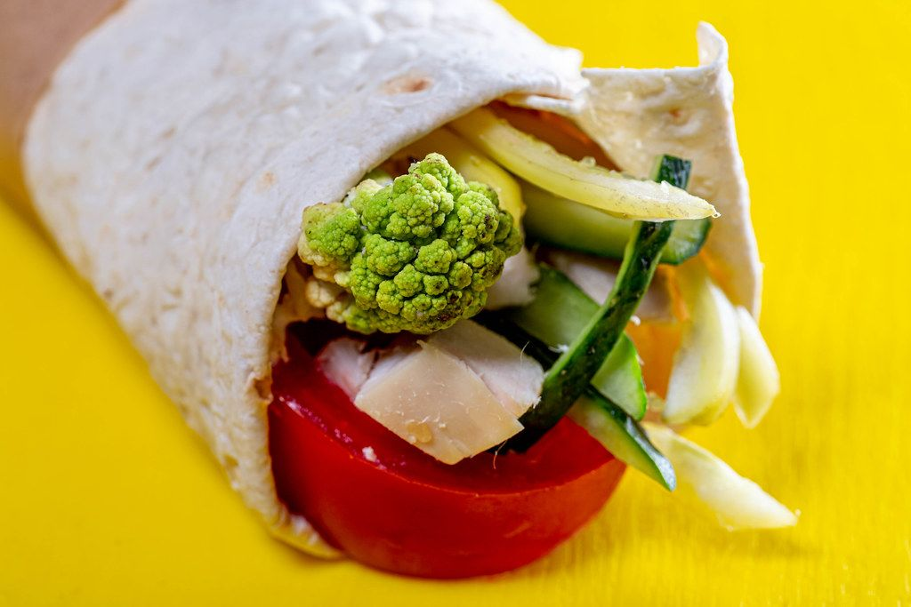 Close-up of vegetables and meat wrapped in pita on yellow background (Flip 2019)